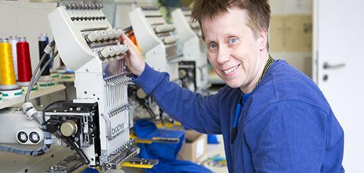 Stickerei Mitarbeiterin an der Stickmaschine